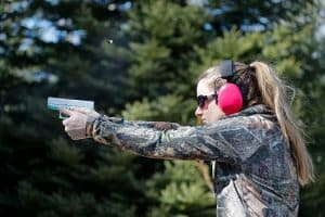 A woman shooting a handgun and the ejected cartridge case in the air
